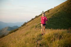 Woman runs on a top of the mountains with mountain range in back Royalty Free Stock Images