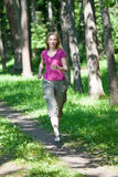 Woman runs on the track in the spring wood Stock Images