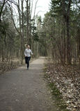 The woman runs on the track in the spring wood Stock Photo
