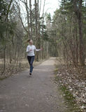 The woman runs on the track in the spring wood Royalty Free Stock Photo