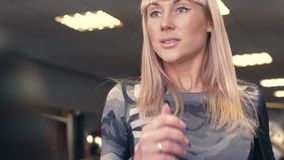 Woman runs on treadmill at the fitness centre. The girl is smiling. 4k stock footage