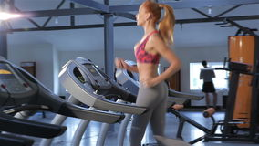 Woman runs on treadmill at the fitness centre stock video footage