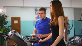 Woman runs on a treadmill, man with tablet manager, a gym sport a healthy lifestyle stock video footage