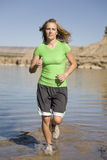 Woman runs in water. A woman wearing green running through the water on rocks at the lake Royalty Free Stock Photos