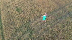 The woman runs on a wheat field. Slow motion stock video