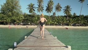 Woman runs on wooden jetty to tropical beach. Young caucasian woman in swimsuit and straw hat happily runs along wooden jetty pier to tropical island coast sandy stock video