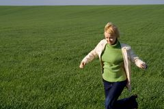 Woman rushing on green field. Young woman rushing through a dark green field in spring - moderate motion blur on the hands royalty free stock photography