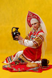 Woman in a russian folk dress. A beautifull woman in a folk russian dress on yellow background Royalty Free Stock Photos