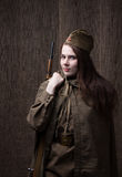 Woman in Russian military uniform with rifle. Female soldier during the second world war. Stock Photos