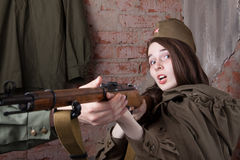 Woman in Russian military uniform shoots a rifle. Female soldier during the second world war. Royalty Free Stock Photos