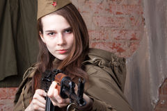 Woman in Russian military uniform shoots a rifle. Female soldier during the second world war. Young woman in Russian military uniform shoots a rifle. Female royalty free stock image