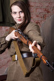 Woman in Russian military uniform shoots a rifle. Female soldier during the second world war. Stock Images