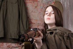 Woman in Russian military uniform shoots a rifle. Female soldier during the second world war. Royalty Free Stock Photography