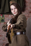 Woman in Russian military uniform shoots a rifle. Female soldier during the second world war. Stock Photos