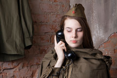 Woman in Russian military uniform speaks on phone. Female soldier during the second world war. Royalty Free Stock Images