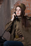 Woman in Russian military uniform speaks on phone. Female soldier during the second world war. Royalty Free Stock Photo