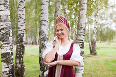 Woman in Russian traditional costume. Is walking on the forest royalty free stock photo
