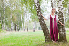 Woman in Russian traditional costume. Is walking on the forest stock photo