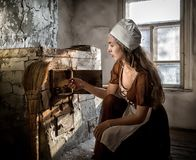 Woman in a rustic dress sitting next to old stove in a ruined abandoned house stock images