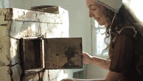 Woman in a rustic dress sitting next to old stove in a ruined abandoned house stock video footage