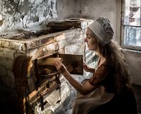 Woman in a rustic dress sitting next to old stove in a ruined abandoned house royalty free stock photo