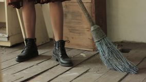 Woman in a rustic dress sweeps the wooden floor in the kitchen stock video