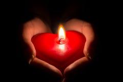 Woman& x27; s递举在黑暗的一个心形的蜡烛 库存图片