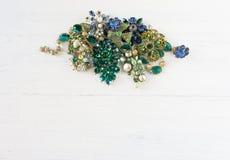 Woman& x27; s首饰 葡萄酒首饰背景 美丽的明亮的假钻石别针、项链和耳环在白色木头 免版税图库摄影