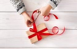 Woman& x27; s вручает оборачивать ленту красного цвета iwith настоящего момента праздника рождества Стоковые Фотографии RF