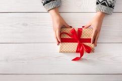 Woman& x27; s вручает оборачивать праздник рождества присутствующий с красной лентой Стоковое Изображение