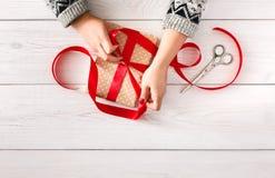 Woman& x27; s вручает оборачивать праздник рождества присутствующий с красной лентой Стоковая Фотография