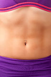 Woman's Abs. Closeup of a fit woman's abs with a pierced belly button Royalty Free Stock Photos