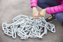 Woman's arms trying to raise a heavy metallic chain. Woman's arms trying to raise a big and heavy metallic chain Royalty Free Stock Photo