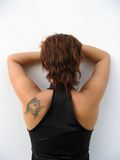 Woman's back. Young woman's back with brown short hair and arms on her face Stock Image