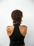 Woman's back. Young woman's back with brown short hair and arms on her shoulders Stock Photos
