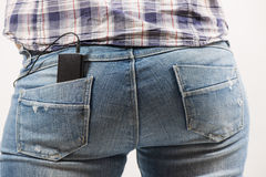 Woman's back in blue jeans with music device Stock Photos