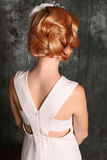 Woman's back view, with red hair in retro style,wears elegant white dress Stock Photo