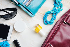 Woman`s bag and it`s content. Phone, lipstick, sunglasses, nail file, nail polish, wallet with cards, box with wet napkins, necklace Royalty Free Stock Photo