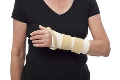 Woman's bandaged arm and wrist in splint. Close-up of senior woman's left arm, bandaged and braced for wrist support after injury stock image