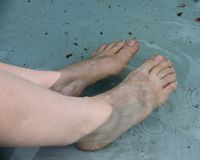 Woman`s bare feet in the fountain water. During the hot summer Royalty Free Stock Image