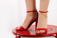 Woman's bare feet in red peep-toes Stock Photography