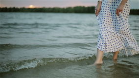 Woman's bare feet in the water of the lake. stock video footage