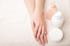 Woman's beautiful hands with care cream bottles Stock Image