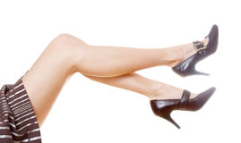 Woman's beautiful legs. In brown striped skirt Stock Images