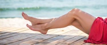 Woman`s beautiful legs on the beach Stock Photo
