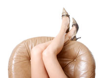 Woman's beautiful long legs. Laying on the brown armchair Stock Photography