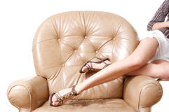 Woman's beautiful long legs. Laying on the brown armchair Stock Photo