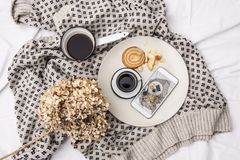 Woman`s bed top view on a lazy sunday morning in cold weather . Lifestyle with mobile phone, book, cakes Royalty Free Stock Images