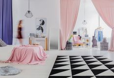 Woman`s bedroom with pink curtains. Triangle carpet in woman`s bedroom interior with pink curtains in entrance to dressing room Stock Images