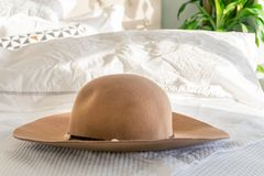 Woman`s beige sun hat with trim and wide brim on a fluffy bed, with sunlight shining indoors. Depicting holidays, relaxation and stock photos